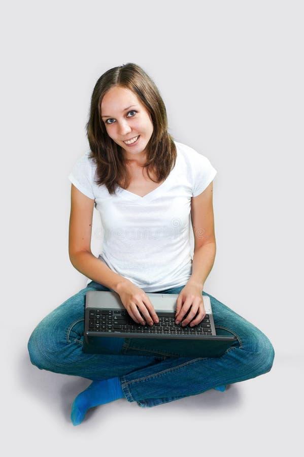 Studencka młoda dziewczyna z laptopem na szarym tle obrazy royalty free