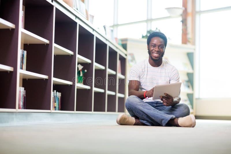 Studencka Używa Cyfrowej pastylka W bibliotece zdjęcia royalty free