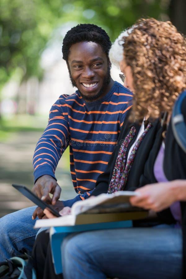 Studencka Używa Cyfrowej pastylka Z przyjaciółmi Dalej zdjęcia stock