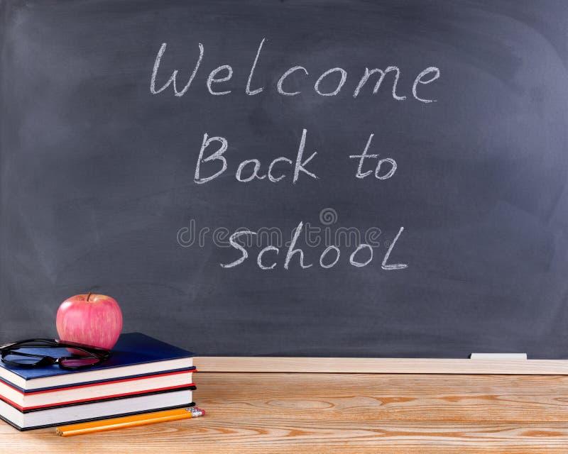 Studencki desktop i wymazujący czarny chalkboard z powitaniem z powrotem zdjęcie royalty free