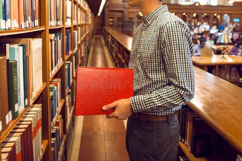 Studencki mężczyzna bierze książkę od półka na książki bibliotecznego publicznie i iść czytać zdjęcia royalty free
