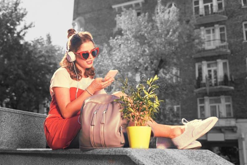 Studencki obsiadanie na zewnątrz dormitorium blisko jej plecaka podczas gdy słuchający muzyka zdjęcia stock