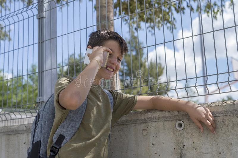 Studencki odpoczywać na szkole i bawić się z telefonem komórkowym obrazy royalty free