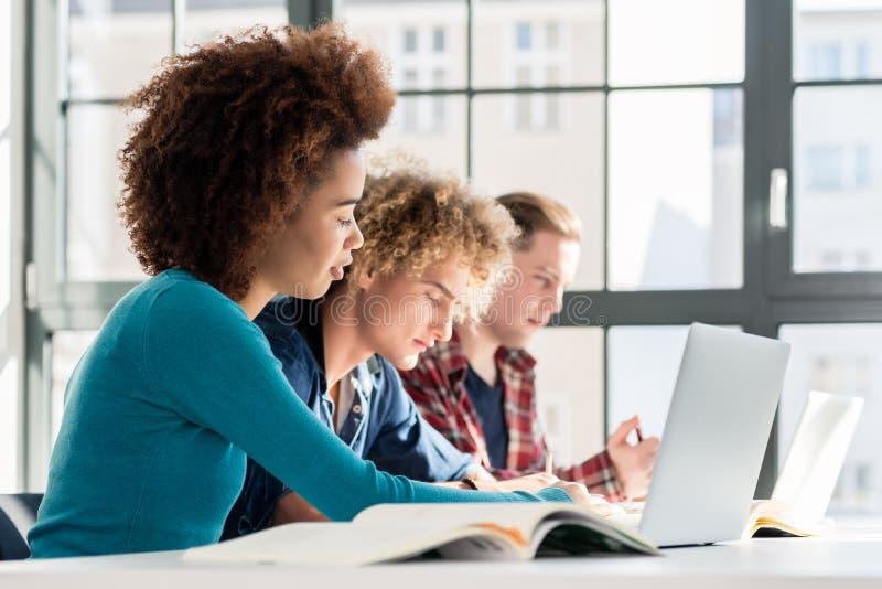 Studencki ono uśmiecha się podczas gdy używać laptop dla online informaci lub v obraz royalty free