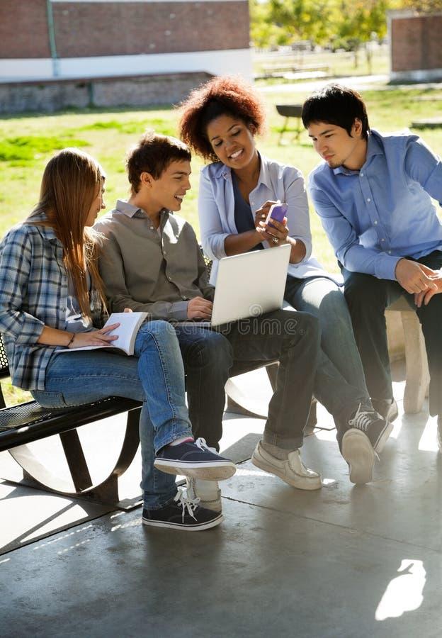 Studencki Pokazuje telefon komórkowy przyjaciele W kampusie fotografia royalty free