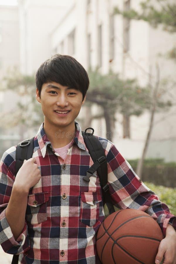 Studencki portret uśmiecha się koszykówkę na szkoła wyższa kampusie i trzyma, fotografia royalty free