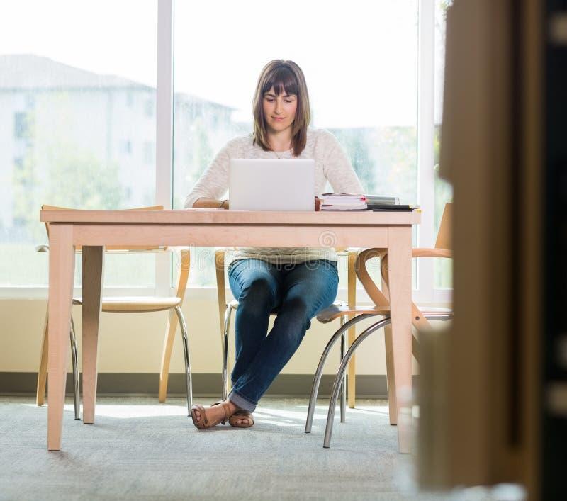 Studencki Używa laptop W bibliotece zdjęcia royalty free