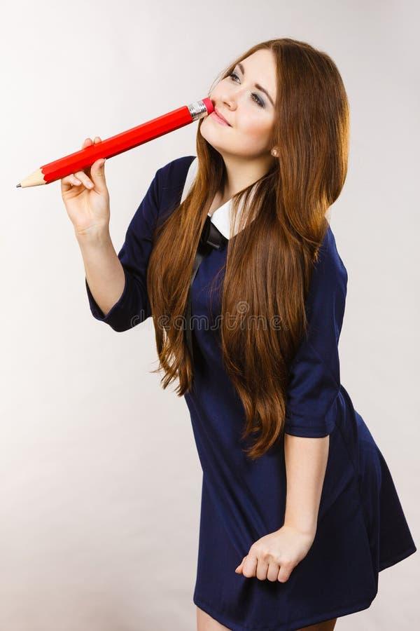 Studenckiej dziewczyny przyglądająca elegancka kobieta trzyma dużego ołówek obraz royalty free