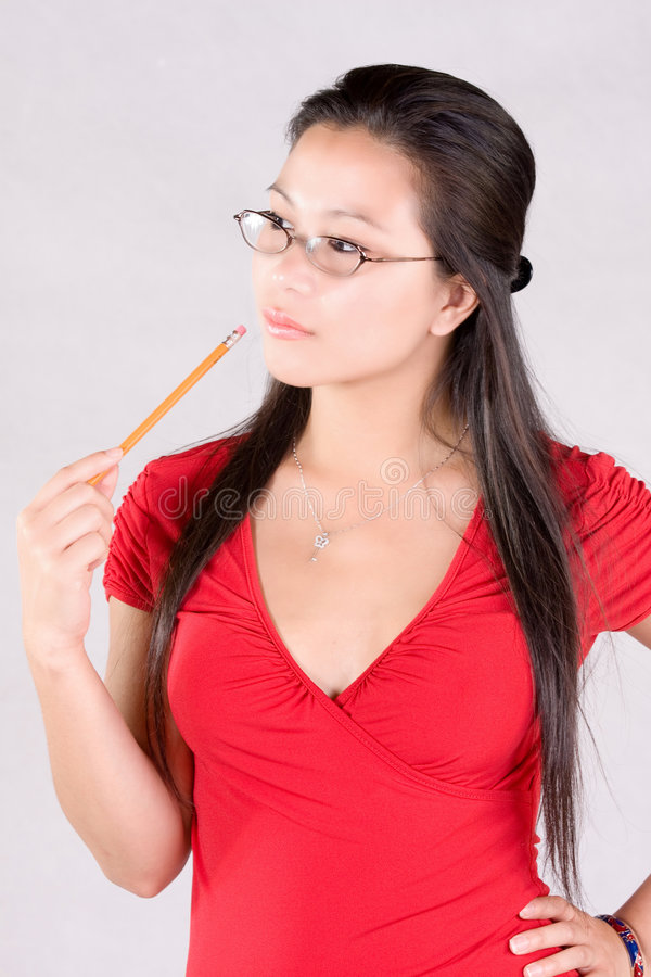 Student. In red outfit holding a pencil stock photo