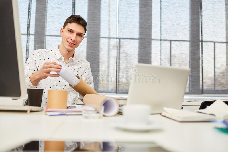 Student with achitectural drawing in place of work royalty free stock images