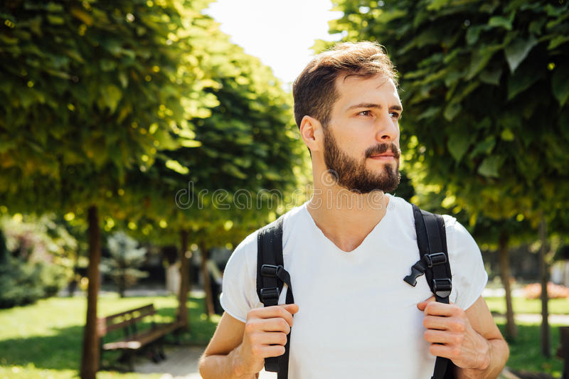 Student with backpack outside. Close up handsome student having backpack standing outside royalty free stock photo