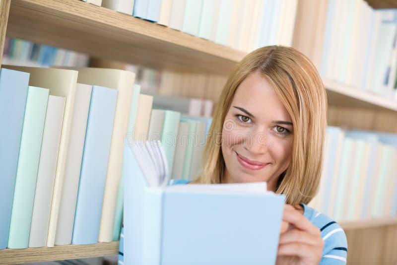 Student in bibliotheek - gelukkige vrouwenstudie van boek royalty-vrije stock afbeeldingen