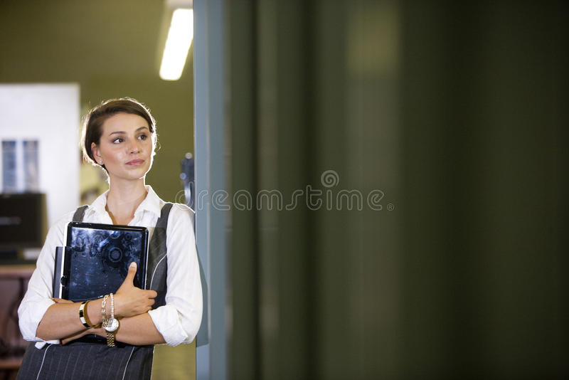 Student bij de holdingslaptop van de bibliotheekdeuropening stock afbeeldingen