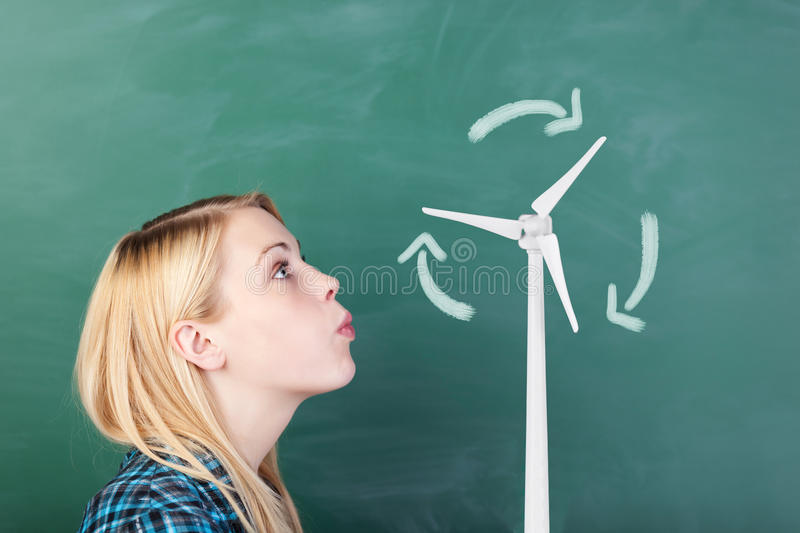 Student Blowing On Wind Turbines Drawn On Chalkboard royalty free stock photos