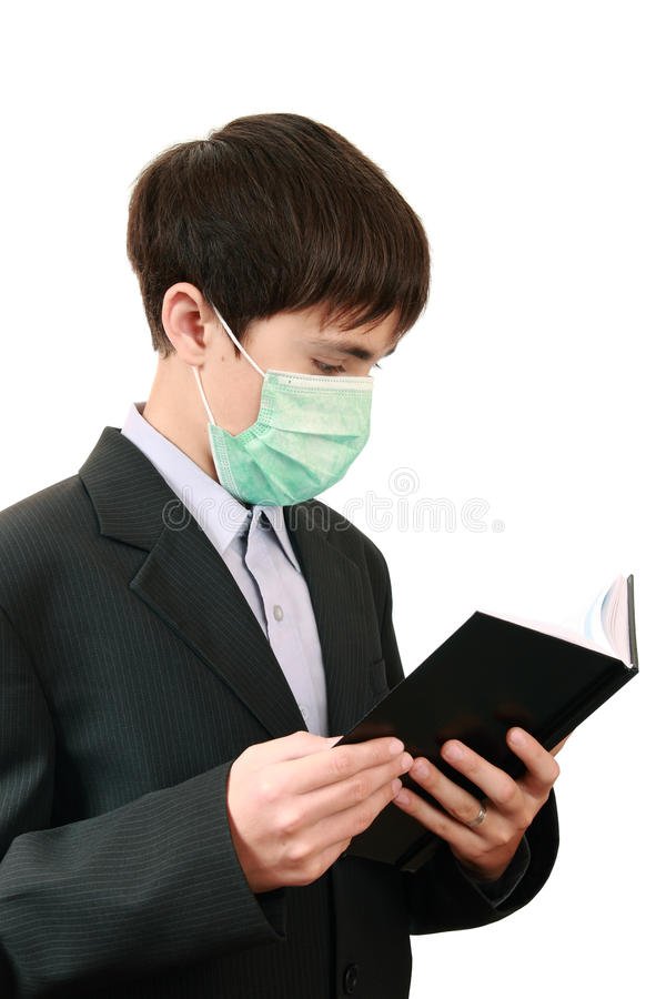 Student with a book in the medical mask