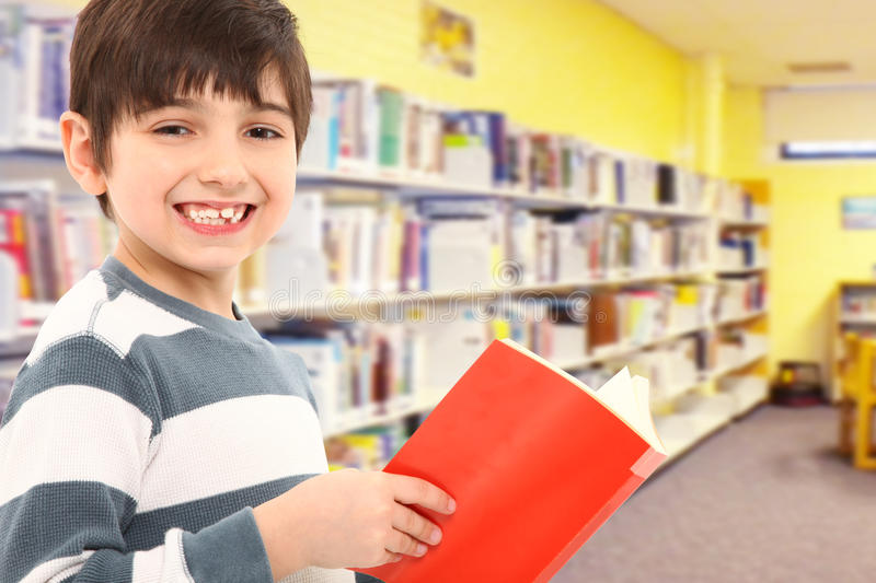 Student with Book in School Library. Attractive 7 year old boy with book in school library smiling at camera royalty free stock images