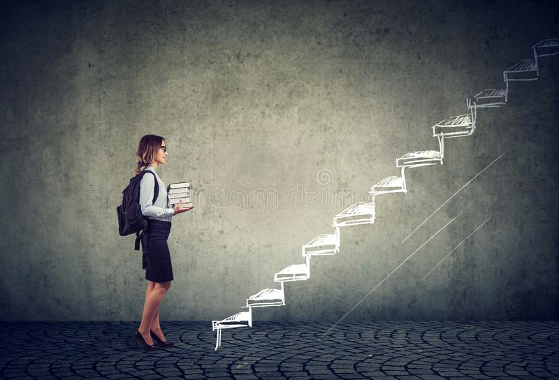 Student with books standing on the stairs of education leading to success stock images