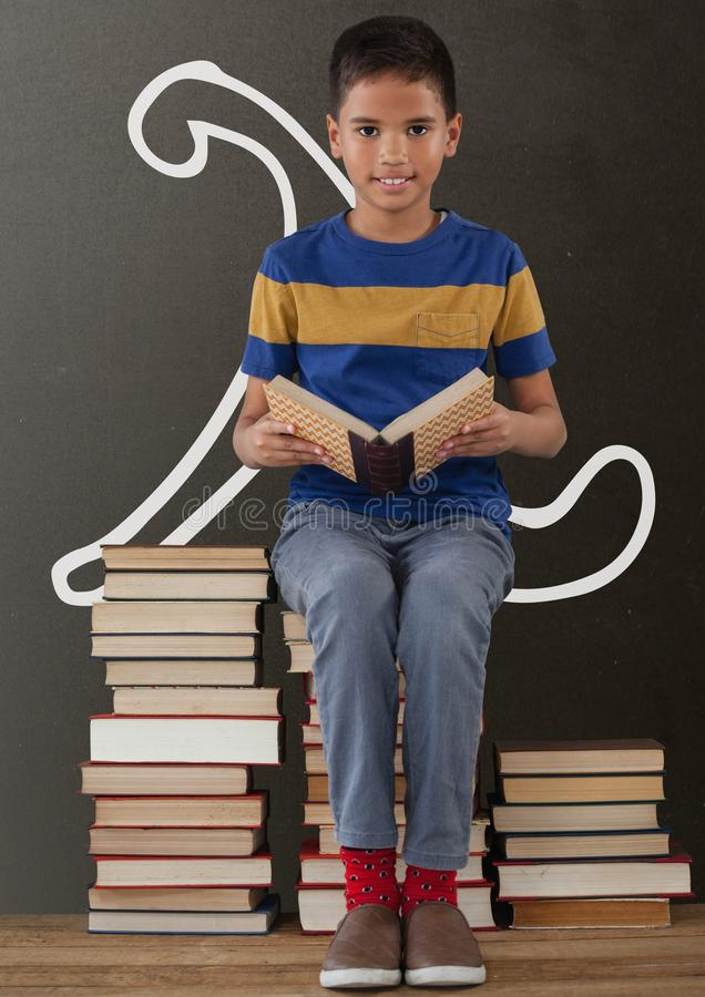 Student boy on a table reading against grey blackboard with school and education graphic stock photography