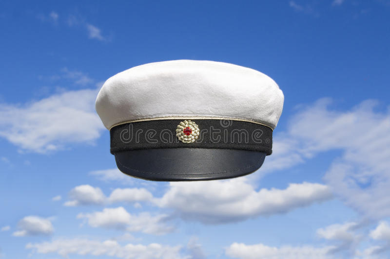 Student cap Swedish on blue sky. Swedish student cap front view on blue sky with some clouds. Red marking and gold ribbon stock photo