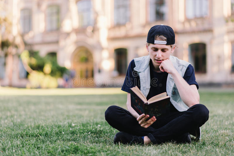 A student carefully reads a book sitting on a grass in a park near a college. Teenager reading a book outdoors royalty free stock images