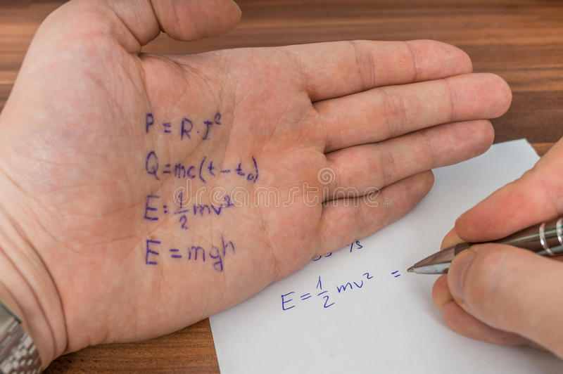 Student is cheating during exam with cheat sheet with formula. royalty free stock photography