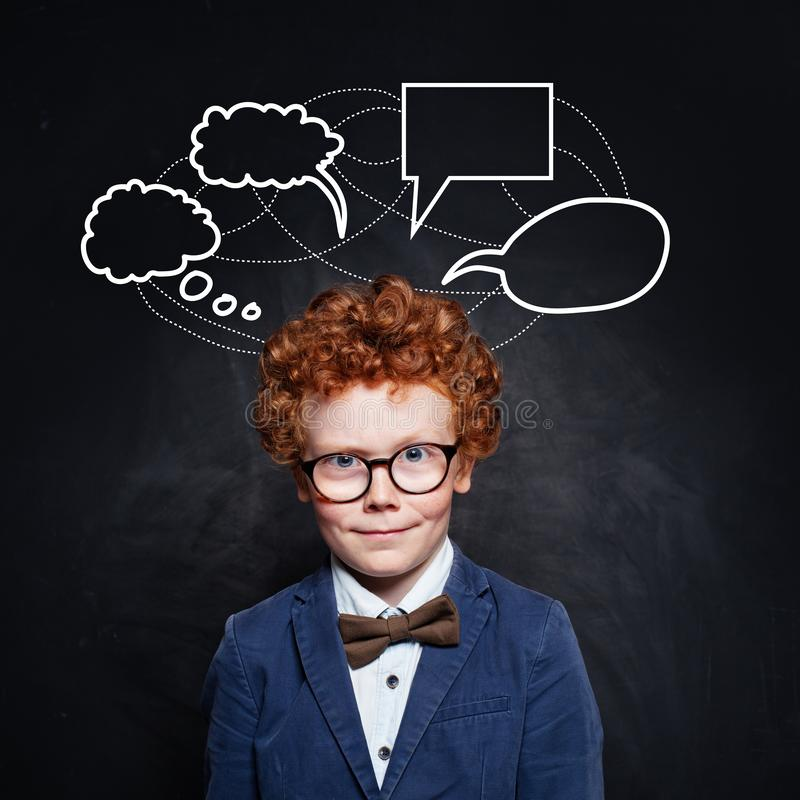 Student child boy in glasses with empty speech clouds bubbles on school background royalty free stock images