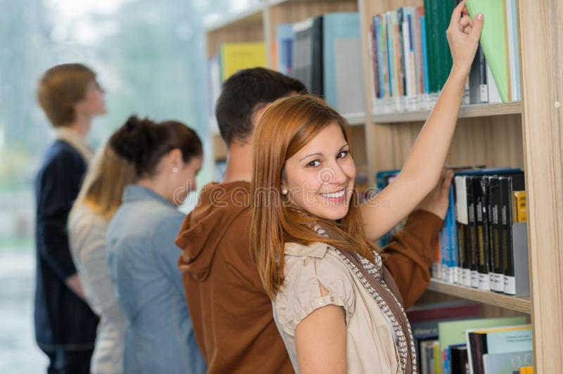 Student choosing book from bookshelf in library stock photo