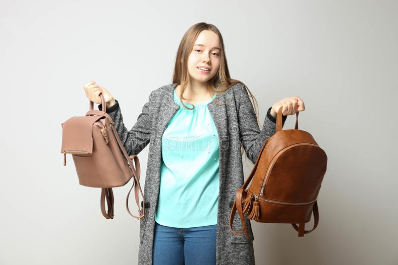 Student in classic casual  clothes with two fashionable backpac. Girl, student in classic casual comfortable clothes with two fashionable backpacks on neutral royalty free stock images