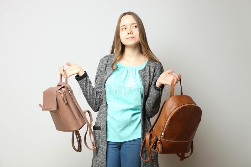 Student in classic casual  clothes with two fashionable backpac. Girl, student in classic casual comfortable clothes with two fashionable backpacks on neutral stock photography