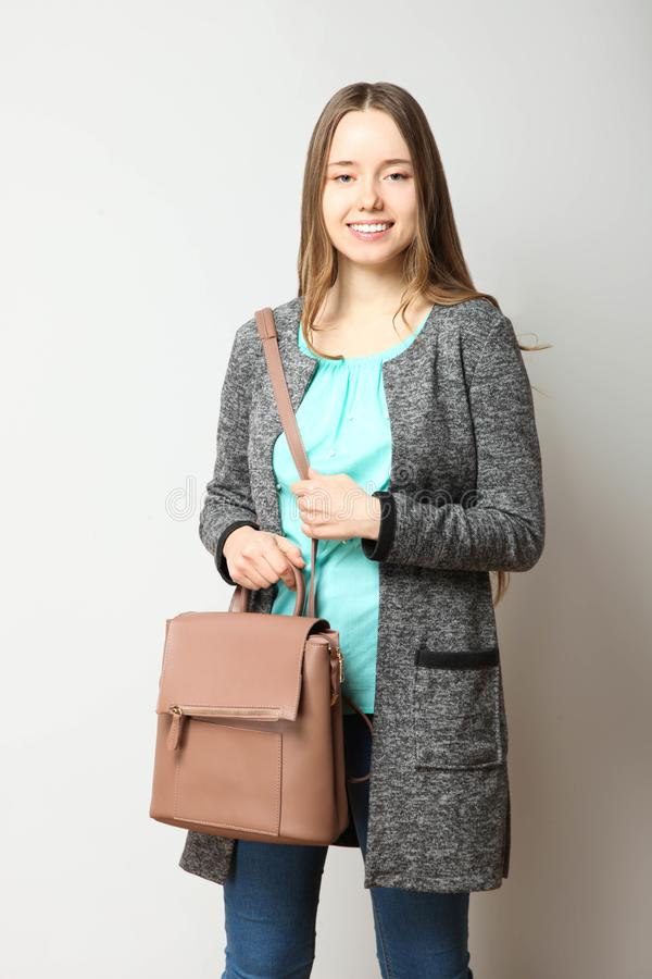 Student in classic casual comfortable clothes with fashionable backpack. Girl, student in classic casual comfortable clothes with fashionable backpack on neutral stock photos