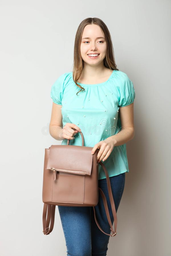 Student in classic casual comfortable clothes with fashionable backpack. Girl, student in classic casual comfortable clothes with fashionable backpack on neutral stock image