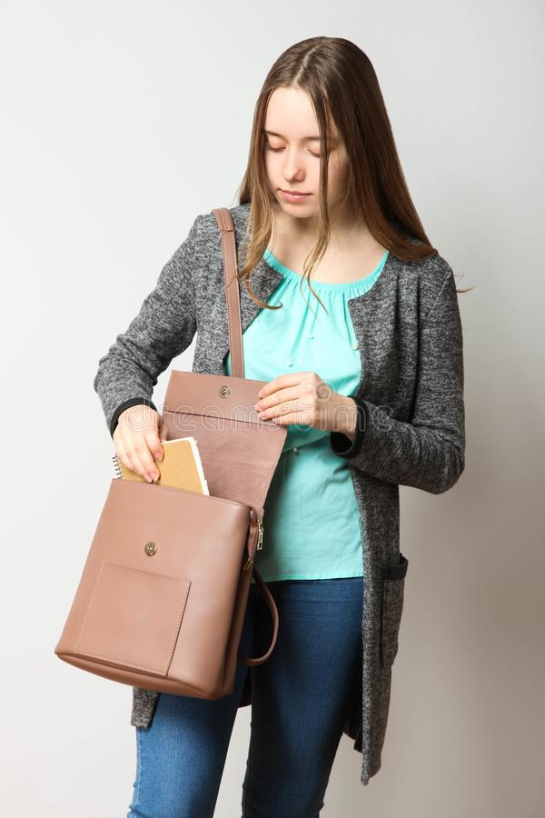 Student in classic casual comfortable clothes with fashionable backpack. Girl, student in classic casual comfortable clothes with fashionable backpack on neutral stock photo