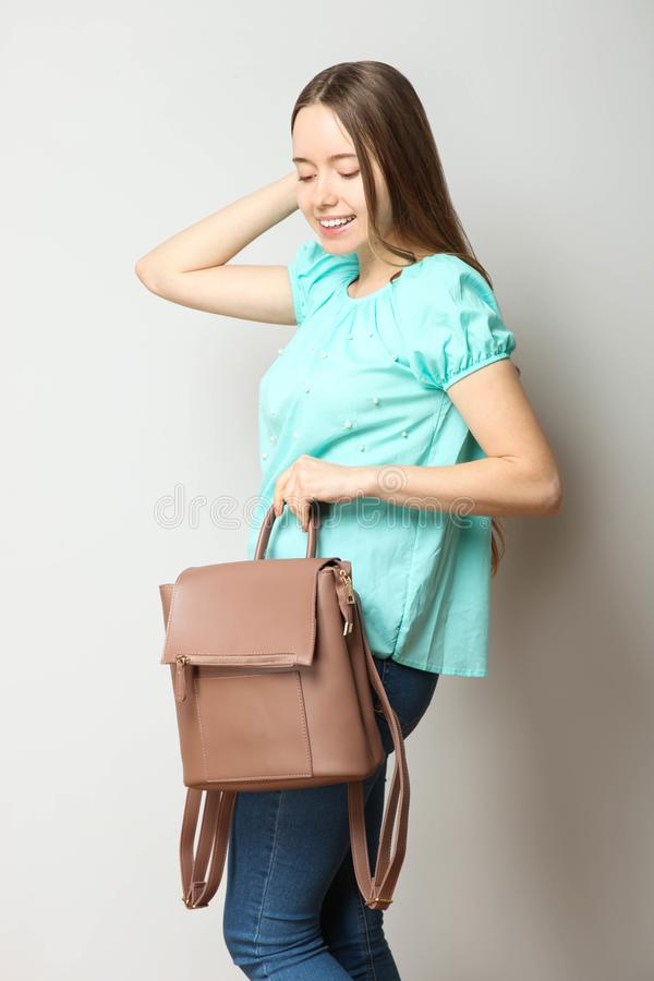 Student in classic casual comfortable clothes with fashionable backpack. Girl, student in classic casual comfortable clothes with fashionable backpack on neutral royalty free stock photos