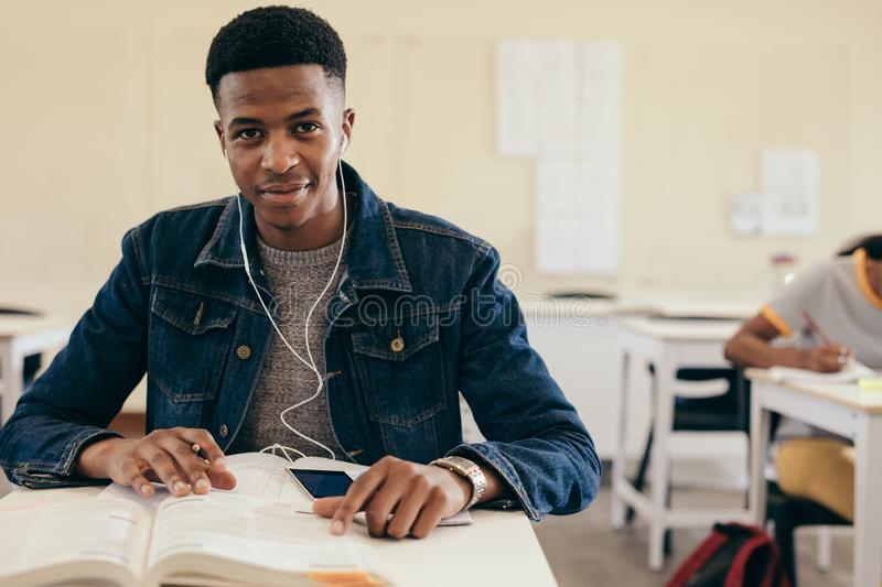 Student in college classroom. African teenage boy sitting in high school classroom with books. Male student with earphones sitting in college classroom royalty free stock photography