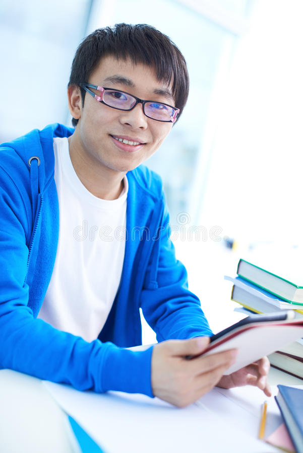 Student in college. Portrait of successful Asian student in eyeglasses looking at camera royalty free stock photo
