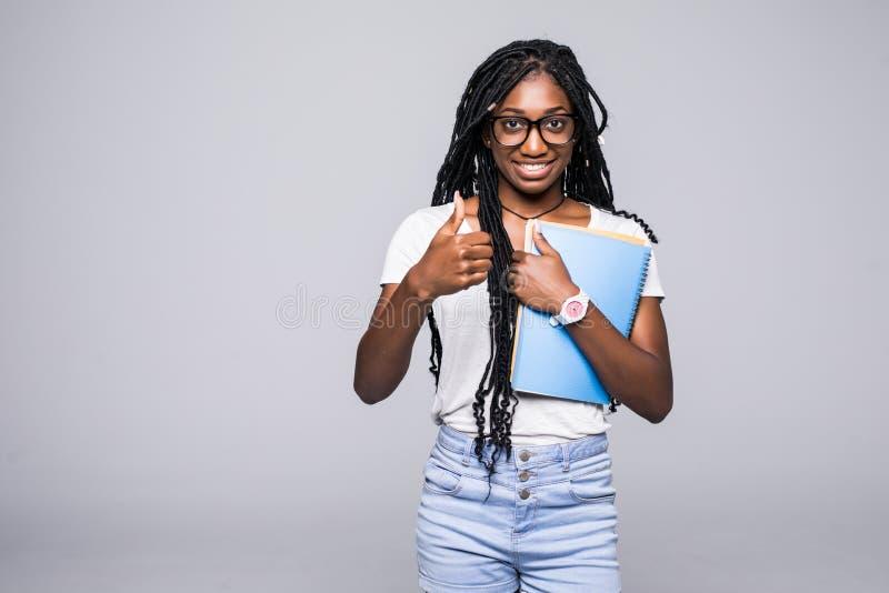 Student collegu amerykanin afrykańskiego pochodzenia młoda kobieta z notatnikiem w rękach odizolowywać na szarym tle obraz royalty free