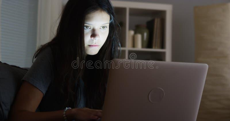 Student collegu pisze jej papierze póżno przy nocą obrazy stock
