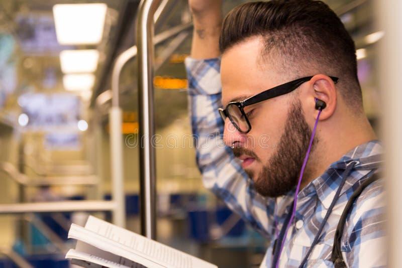 Student collegu studiuje z szkłami podczas gdy jadący uniwersytet metrem Pojęcie dojeżdżać do pracy, dedykacja, wysiłek, studia zdjęcia stock