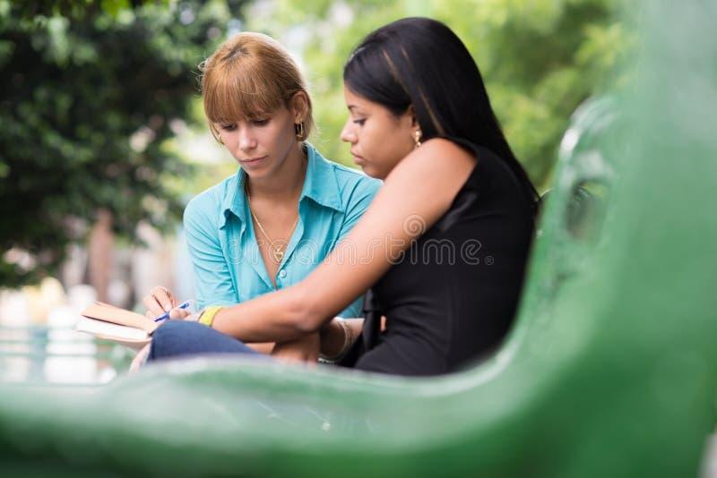 Student collegu target1042_1_ na podręczniku w parku zdjęcia royalty free