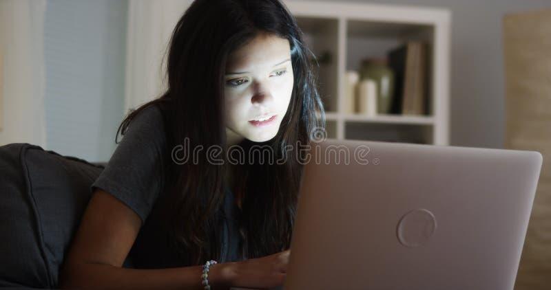 Student collegu zostaje up opóźnionego writing jej papier na laptopie zdjęcia stock