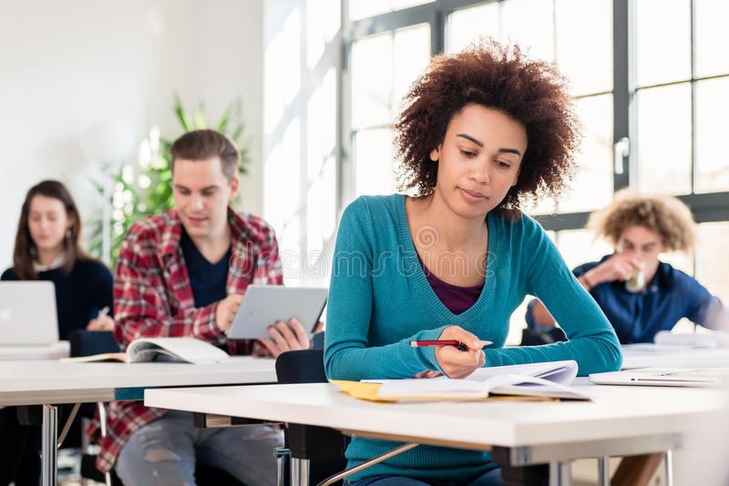 Student concentrating while writing an essay during class in an. Young female student with a serious facial expression concentrating while writing an essay stock photography