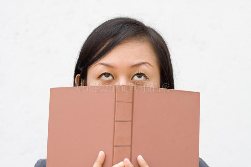 Student covering her face with book royalty free stock images