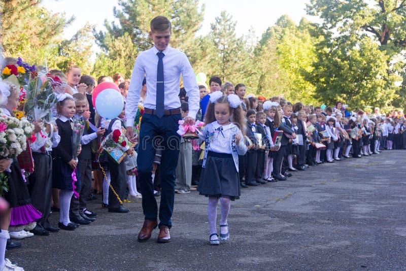 Student den höga gruppen och flickan enväghyvel med en klocka i hennes hand på skolan den högtidliga linjalen i dag av kunskap royaltyfri foto