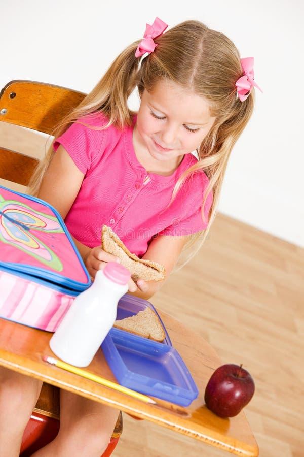 Student: Den hungriga flickan sitter på skrivbordet som äter lunch arkivfoto