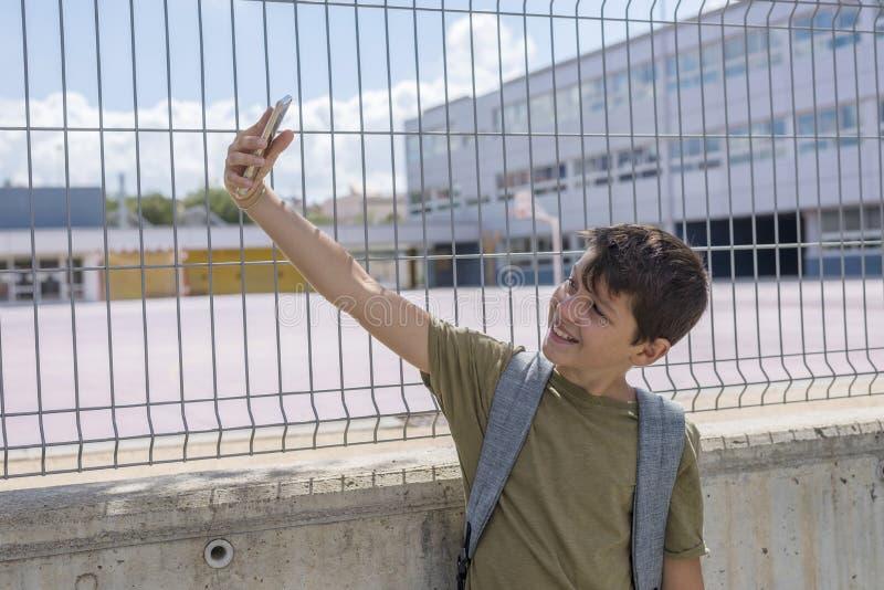 Student, der außerhalb einer Schule stillsteht und mit einem Handy spielt stockfotos
