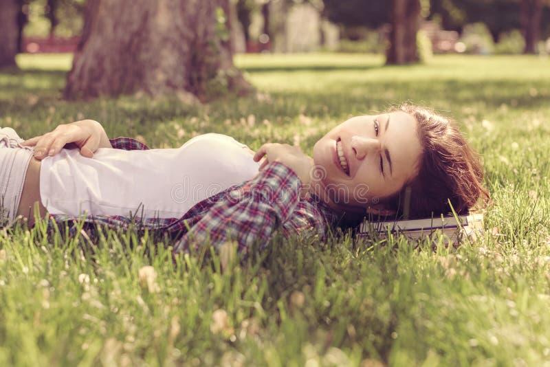 Student, der auf dem Gras im Park stillsteht ihren Kopf auf dem b liegt stockbild