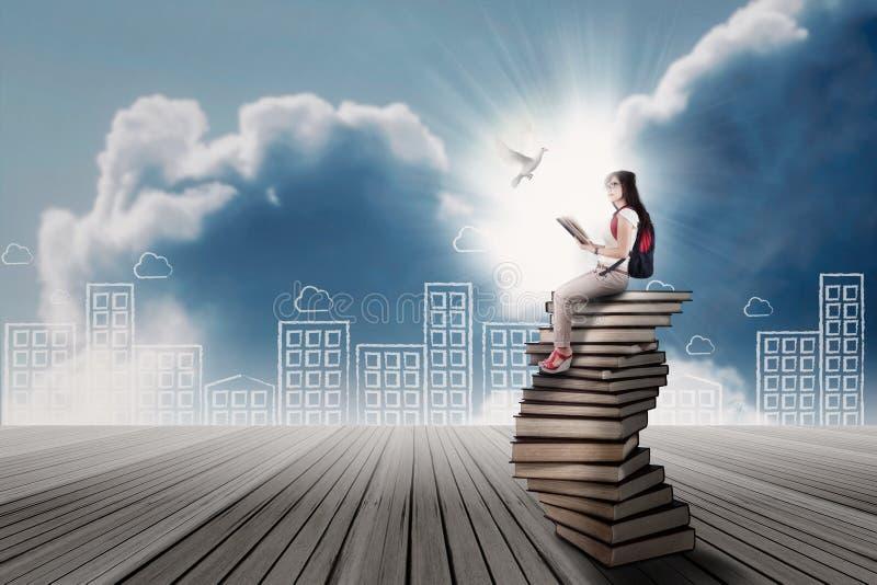 Student, der auf einem Stapel Büchern sitzt stockbild