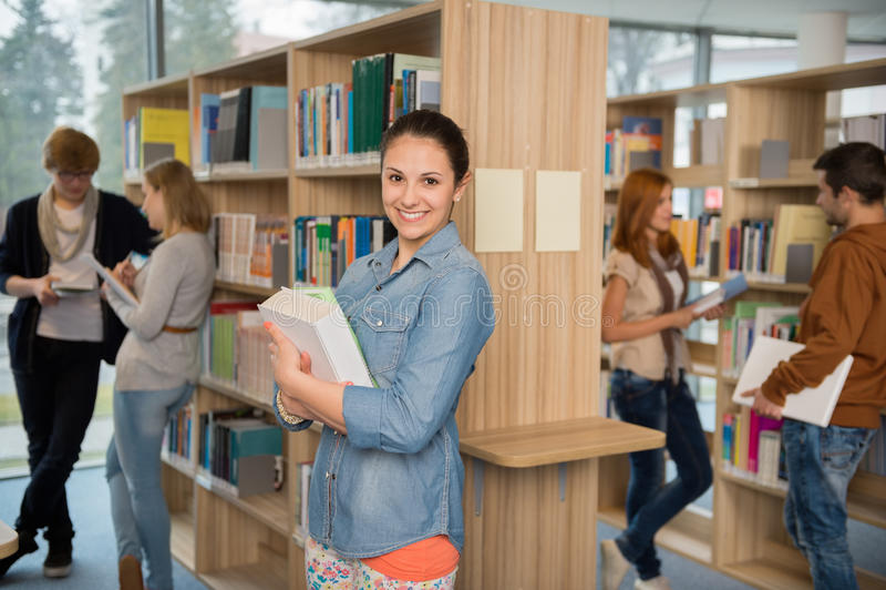 Student, der Bücher in der Bibliothek hält stockfotografie
