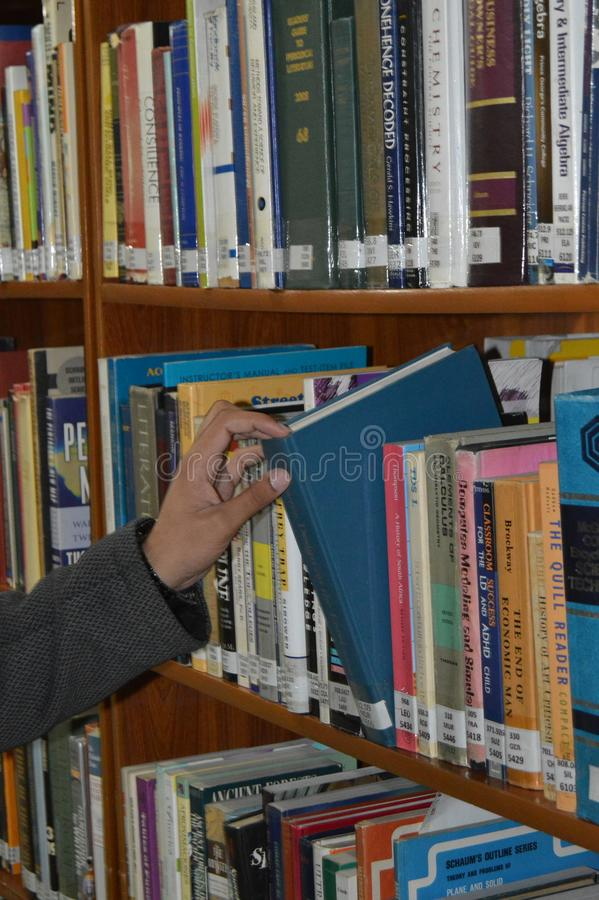 Student, der Buch vom Regal in der Bibliothek herausnimmt stockfoto