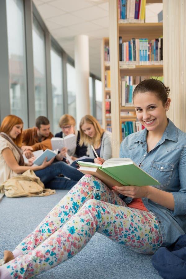 Student, der in der Schulbibliothek mit Freunden sitzt lizenzfreie stockfotos